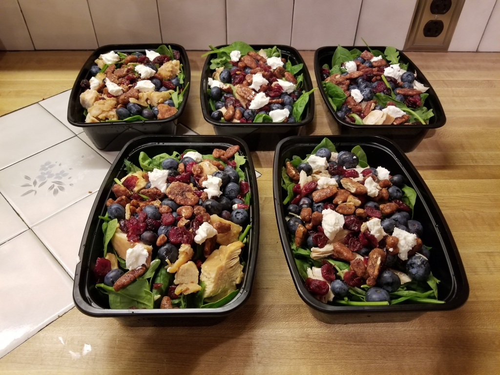 Arugula, spinach, blueberry, goat cheese, chicken, and craisin salad lunch prep.