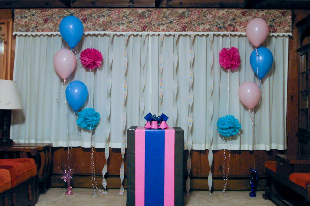The gender reveal box sits between pink and blue balloons and tissue paper flowers.